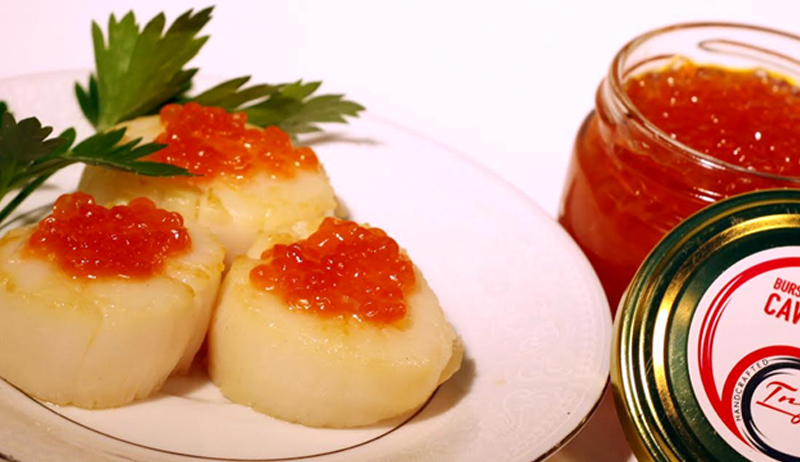 Scallops topped with red caviar